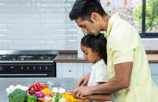 Father teaching his daughter cooking